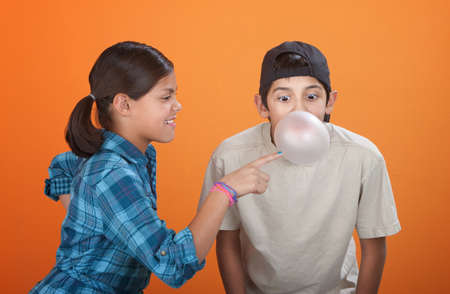 Girl touching a bubble blown by her brother with chewing gum