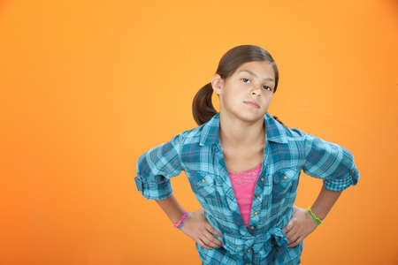 Young girl on orange background with hands on hips Stock Photo - 8925078