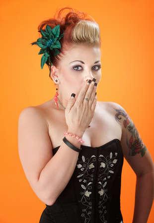 guardar silencio: Mujer extravagante sorprendida con la mano en la boca