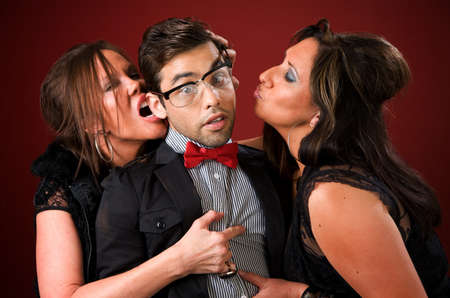 nerd girl: Two aggressive cougar women corner a shy young man Stock Photo