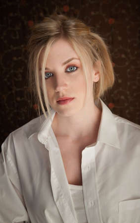 Serious young blonde girl in a white shirt