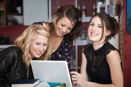 Group of young women having a good time while sitting around a laptop photo