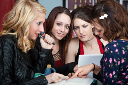 Group of female teen friends reading through a textbook photo