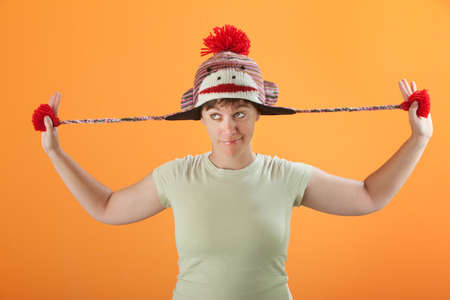 fiddles: Young Caucasian woman fiddles with her sock monkey cap