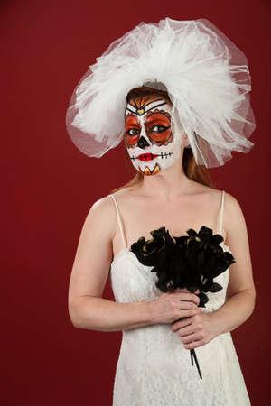 Bride in makeup with a bunch of black roses for Dia De Los Muertos photo
