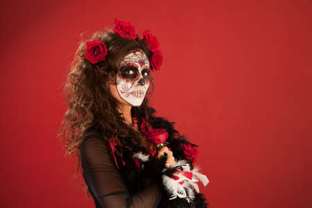 Woman in makeup for Dia De Los Muertos holds a rose close to herself photo