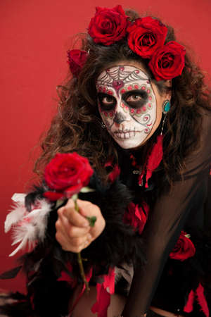 Woman dressed for All Souls Day holding out a red rose photo