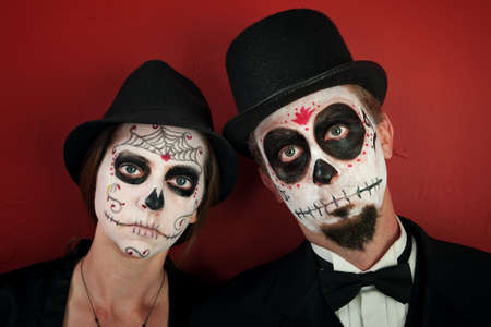 cobweb: Serious couple in skull and cobweb makeup with hats