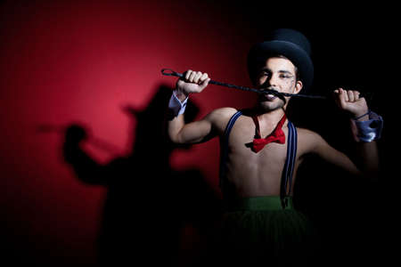 Performer in top hat biting leather whip photo