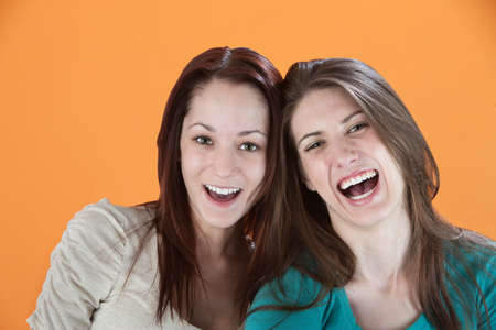 Two girlfriends on an orange background laugh photo