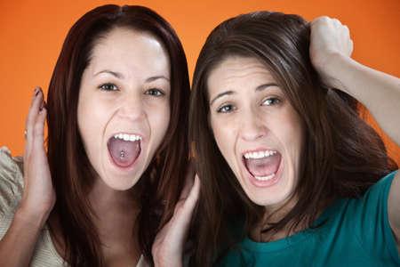Pair of women on orange background get upset photo
