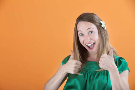 overly: Overly enthusiastic woman in green blouse with thumbs up
