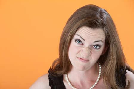 Mean-looking Caucasian woman in dress on orange background