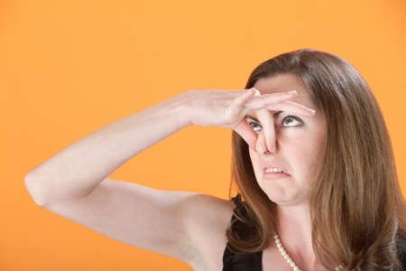 Young Caucasian woman on orange background holds her nose