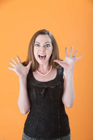 Scared Young Caucasian woman on an orange background photo