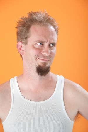 wifebeater: Uomo caucasica infastidito con capelli disordinati su sfondo arancione