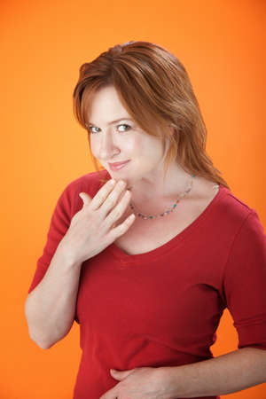 Slightly embarrassed Caucasian woman on orange background photo