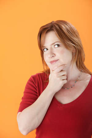 lost in thought: Caucasian woman lost in thought on an orange background Stock Photo