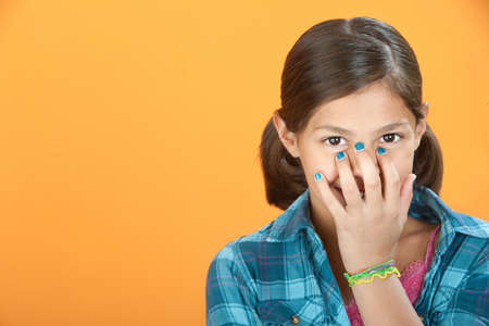 stifle: Little Hispanic girl covers a smile with her hand