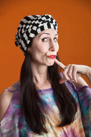 duh: Hispanic woman in tie-dye shirt thinking about something Stock Photo