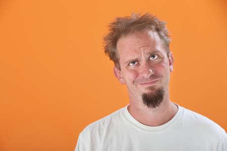 wifebeater: Infastidito uomo caucasica alzando lo sguardo su uno sfondo arancio Archivio Fotografico