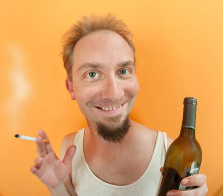Caucasian man holding a cigarette and a alcohol bottle with a big smile