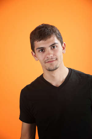 Confident and handsome Mexican American teen isolated on an orange background