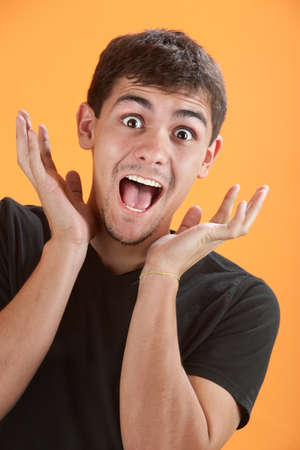 uncontrollable: Young Latino man is very excited with hands near head Stock Photo