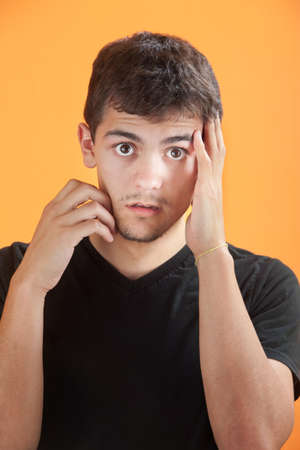 Young Mexican American man with his hand on his face Stock Photo