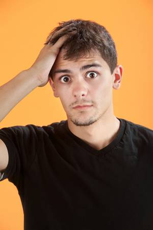 remorse: Forgetful Native American teen on orange background Stock Photo