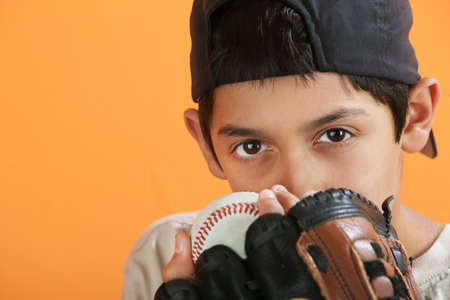 Young Hispanic male with baseball, mitt and backwards hat photo
