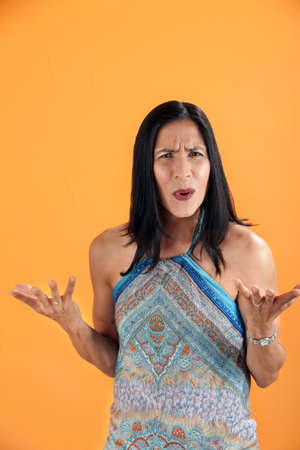 i t: Latina Woman with a puzzled look on an orange background