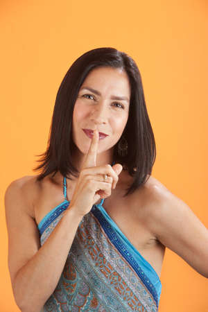 Young attractive Native American woman with finger to her lips