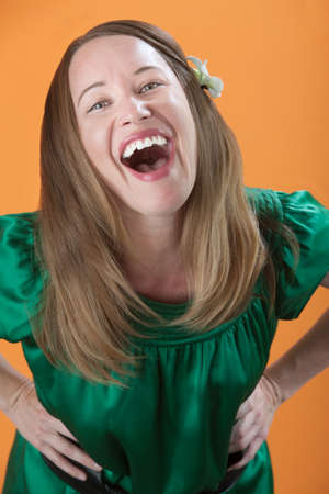Beautiful Caucasian woman laughing loud out on an orange background