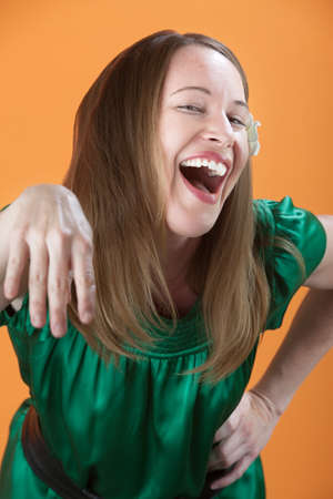 Laughing Caucasian woman sticks her hand out photo