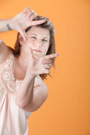 Caucasian woman frames her face on an orange background photo