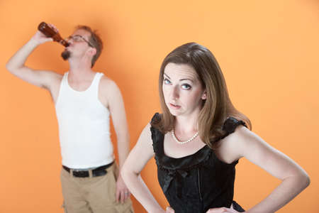 Unhappy Caucasian wife with alcoholic husband on orange background Stock Photo