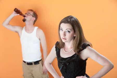 slob: Unhappy Caucasian wife with alcoholic husband on orange background Stock Photo