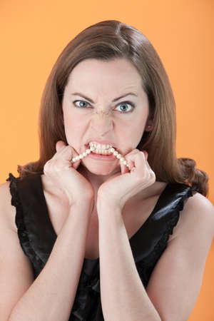 Angry young Caucasian woman biting her necklace  photo