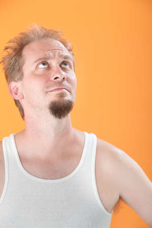 wife beater: Worried Caucasian man on orange background looks up