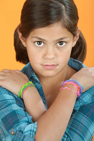 wristbands: Little Hispanic Girl with arms crossed on an orange background
