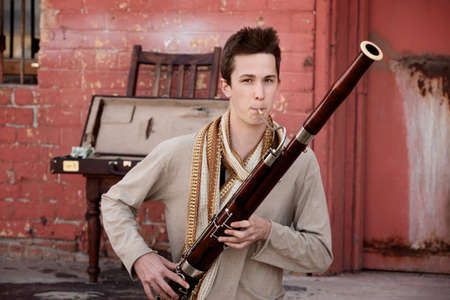 rehearse: Handsome young Caucasian man in Indian attire plays a Bassoon