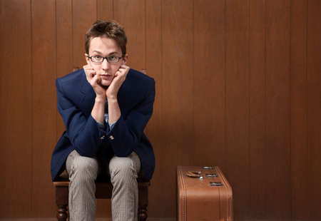 Serious Caucasian male with chin in hands and suitcase Banque d'images