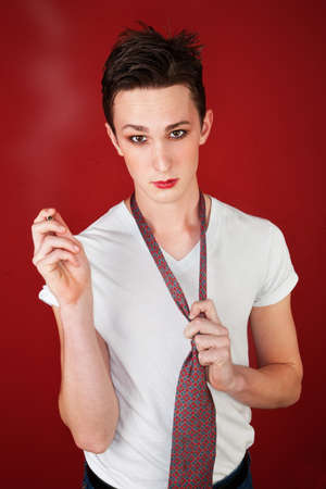 Young man on red background holds a tie and points a cigarette photo