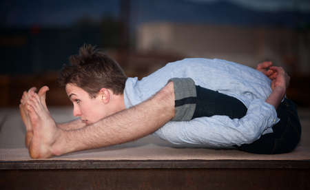 bend: Young flexible Caucasian man exercising outside on a yoga mat