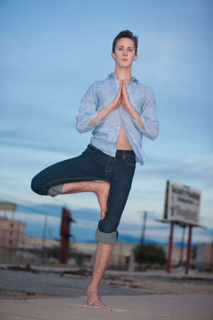 Young Caucasian man doing the Vrksasana yoga posture outside photo