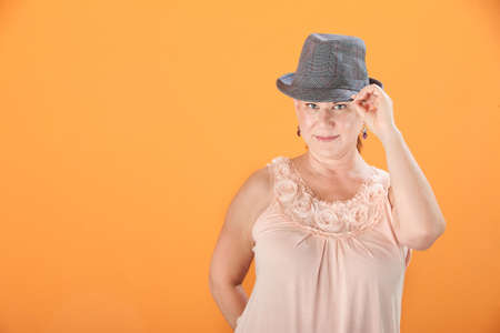 Middle-aged Caucasian woman on orange background tips her hat photo