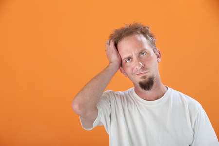 Caucasian man with goatee and hand on his head