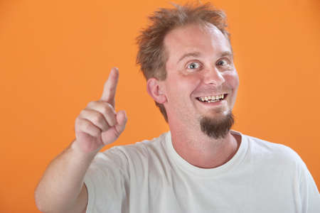 Happy Caucasian man points index finger upward photo