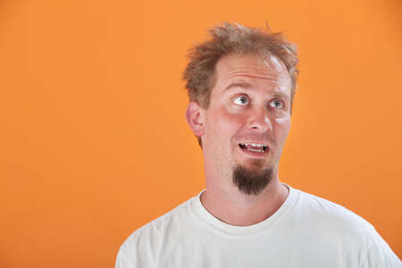 Disinterested Caucasian man with goatee on an orange background photo